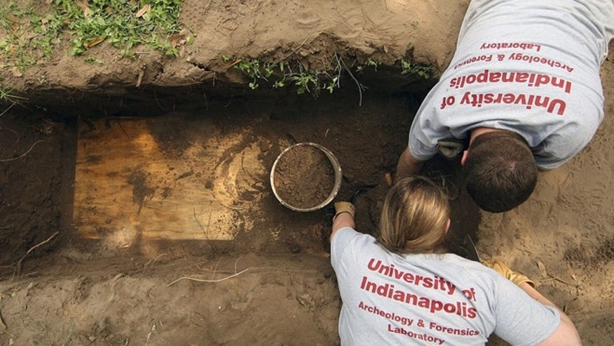 FILE: Members of the University of Indianapolis archeology & forensics laboratory, dig up a casket containing the remains of unidentified immigrants at the Sacred Heart Burial Park in Falfurrias,Texas.