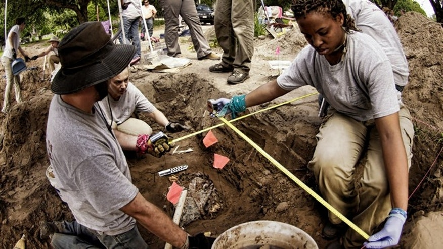 June 5: Forensic team members record measurements from an archeological dig at the Sacred Heart Burial Park in Falfurrias, Texas, where the graves of unidentified immigrants have been found.