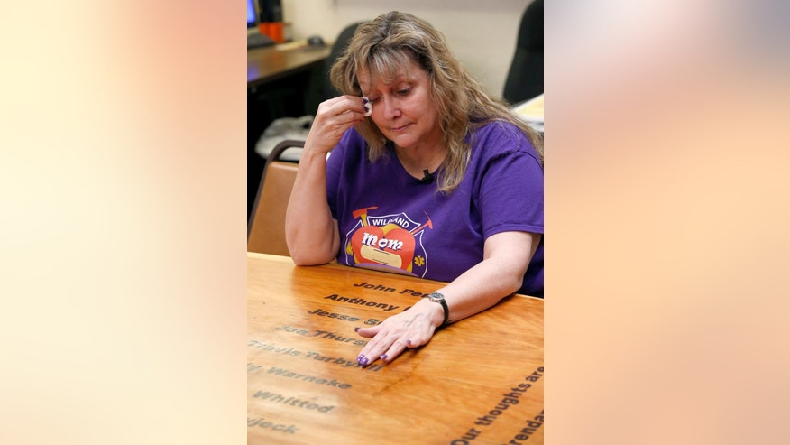 In her first visit back to the firehouse since her son's death, Colleen Turbyfill, Travis Turbyfill's mother, is overcome with emotions as she rubs her fingers over her son's name on an inscribed wooden table, as she recalls memories of her and her son, who was killed along with 18 other hotshots during a wildfire nearly a year ago, on Tuesday, June 24, 2014, in Prescott, Ariz. (AP Photo/Ross D. Franklin)