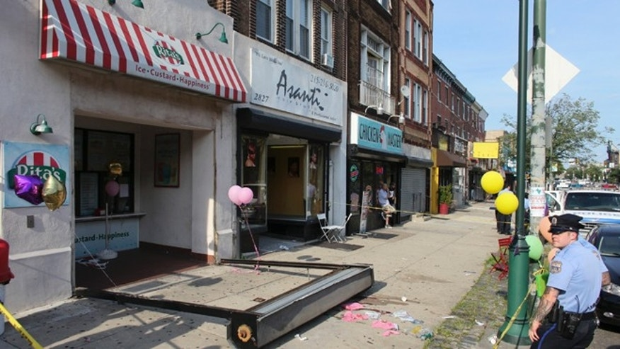 June 28, 2014: Investigators look over the debris of a fallen security door outside a Rita's Water Ice store in the Brewerytown section of Philadelphia.
