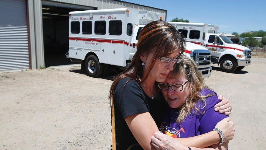 In this Tuesday, June 24, 2014 photo, in her first visit to the firehouse in Prescott, Ariz., since her son's death, Colleen Turbyfill, right, Travis Turbyfill's mother, gets a hug from Katie Cornelius, Prescott Fire Department volunteer exhibit curator for the Tribute Fence Preservation Project, after Turbyfill visited the Granite Mountain Hotshots crew vehicle buggy where her son Travis sat before he was killed along with 18 other hotshots in a wildfire almost a year ago. (AP Photo/Ross D. Franklin)