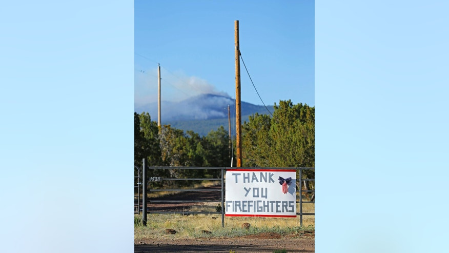 A sign, thanking firefighters is posted along the road near the San Juan Fire Sunday, June 29, 2014 in Vernon, Ariz.  The wildfire that has charred nearly 8 square miles in eastern Arizona's White Mountains held steady Saturday, though the human-caused blaze has not been brought under control at all, officials said.  (AP Photo/The Arizona Republic, David Kadlubowski)  MARICOPA COUNTY OUT; MAGS OUT; NO SALES