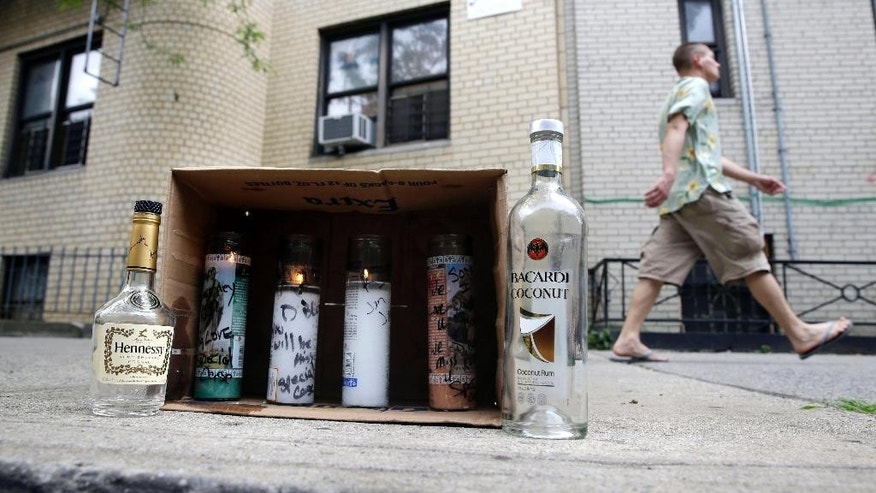 A man walks past a small memorial that was placed near the site of a fatal shooting in the Bronx section of New York, Monday, June 30, 2014.  Authorities say at least 21 people were shot across New York City over the weekend. (AP Photo/Seth Wenig)