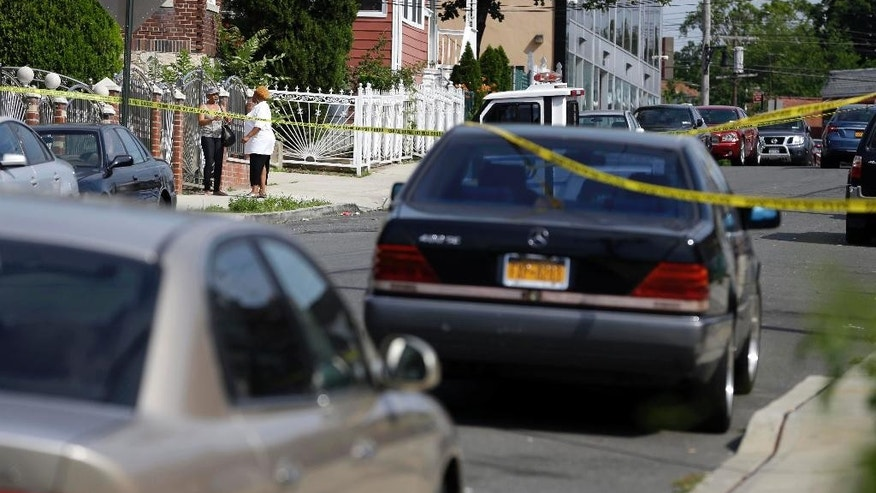 Two women talk near a crime scene where a man was discovered shot and subsequently died in the Bronx section of New York, Monday, June 30, 2014.  Authorities say at least 21 people were shot across New York City over the weekend. (AP Photo/Seth Wenig)