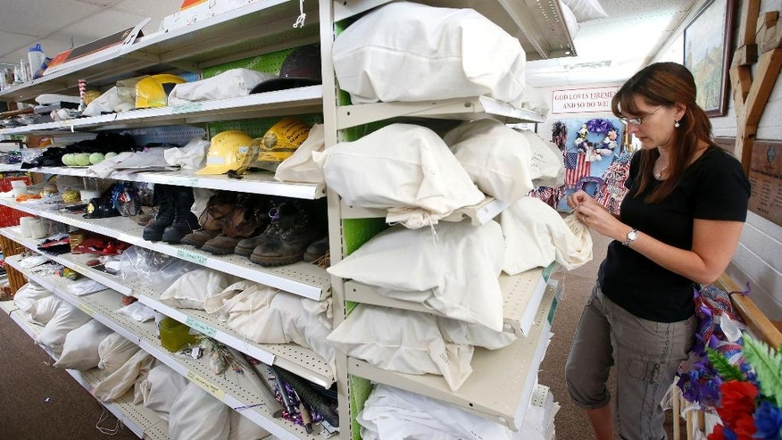 Katie Cornelius, the volunteer exhibit curator for the Tribute Fence Preservation Project, looks through a section of hats among the thousands of artifacts saved from the tribute honoring the 19 Granite Mountain Hotshots killed nearly a year ago fighting a wildfire on Tuesday, June 24, 2014, in Prescott, Ariz. (AP Photo/Ross D. Franklin)