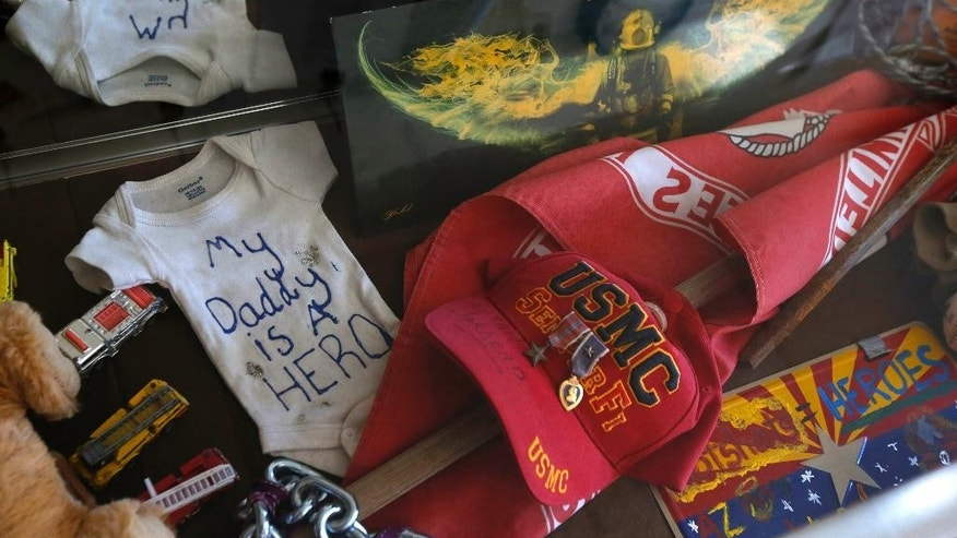 Memorabilia saved from the makeshift memorial honoring the 19 Granite Mountain Hotshots killed nearly a year ago fighting an Arizona wildfire, is now part of the a preservation project on Tuesday, June 24, 2014, in Prescott, Ariz. (AP Photo/Ross D. Franklin)