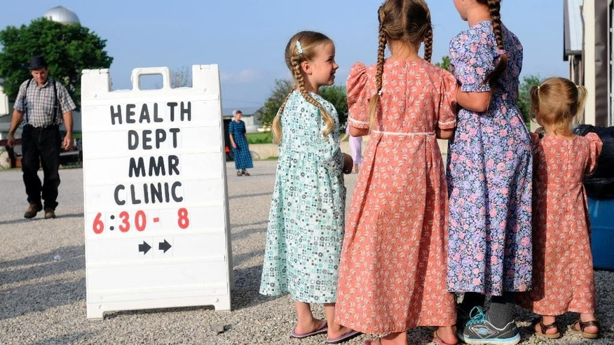 In this June 25, 2014 photo, young Mennonite girls gather at the health and safety clinic, which included a Measles, Mumps, & Rubella vaccinations in Shiloh, Ohio. Health officials said Ohio's current outbreak of measles consists of more than 360 cases and is the biggest in the U.S. since 1994. The outbreak started after Amish travelers to the Philippines contracted measles this year and returned home to rural Knox County Ohio. (AP Photo/Tom E. Puskar)