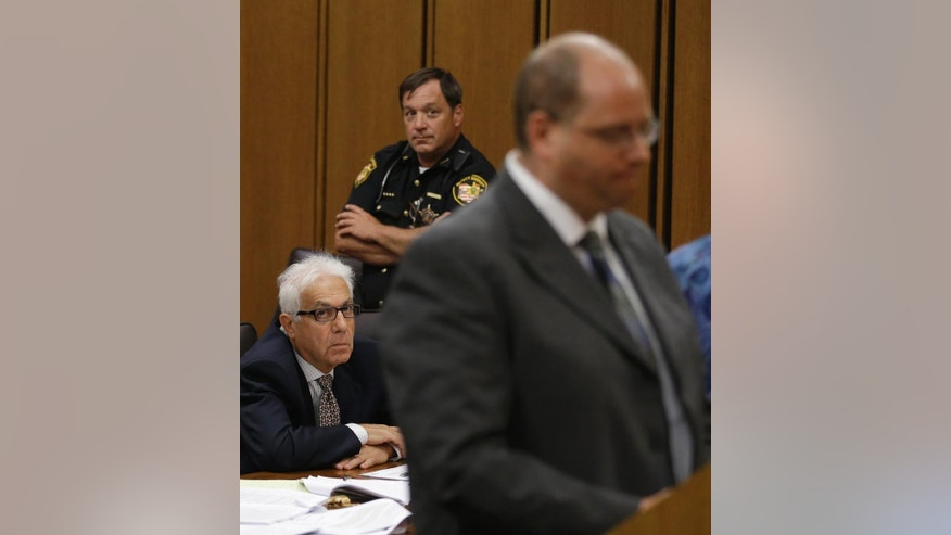 Dr. Georges Bensimhon, left, looks at Seth Hoffer making a statement to the court during Bensimhon's sentencing Tuesday, July 1, 2014, in Cleveland. Bensimhon, a Pennsylvania anesthesiologist, was sentenced to 3 years in prison for what prosecutors believe was an attempt to kill his son-in-law, Hoffer, who also is a doctor, in a Cleveland suburb in September 2013. Bensimhon pleaded guilty to a single count of felonious assault in April. (AP Photo/Tony Dejak)
