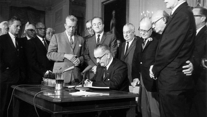 FILE - This July 2, 1964 file photo shows President Lyndon Baines Johnson signing the Civil Rights Act in the East Room of the White House in Washington. Standing, from left, are Sen. Everett Dirksen, R-Ill.&#x3b; Rep. Clarence Brown, R-Ohio&#x3b; Sen. Hubert Humphrey, D-Minn.&#x3b; Rep. Charles Halleck, R-Ind.&#x3b; Rep. William McCullough, R-Ohio&#x3b; and Rep. Emanuel Celler, D-N.Y. The Civil Rights Act of 1964 is considered one of the most celebrated legislative achievements in U.S. history. Signed on July 2, 1964 by President Lyndon B. Johnson, this law made it illegal to discriminate on the basis of race, color, religion, sex, or national origin, and barred unequal application of voter registration requirements. (AP Photo, File)