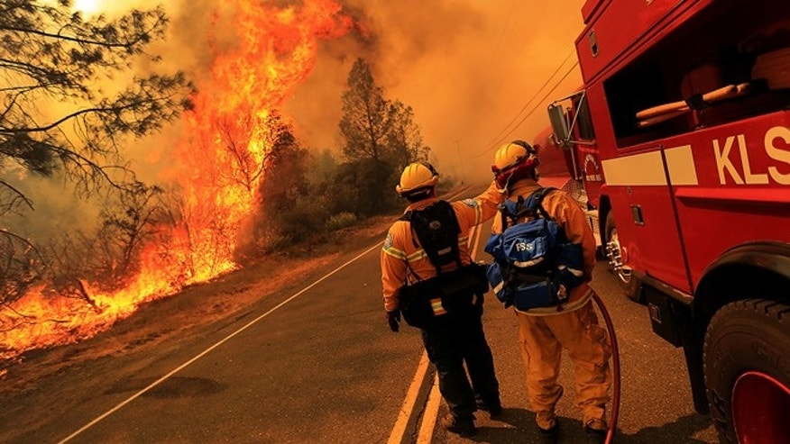 July 1, 2014: Kelseyville firefighters prepare to pull back from the fire on Butts Canyon Road as the fire jumps the road outside Middletown, California at the border between Lake and Napa counties.