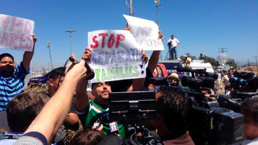 Counter-protestors hold pro-immigrant banners as protestors stand in the road blocking a bus carrying 140 immigrants on the way to be processed at the Murrieta border patrol station on Tuesday, July 1, 2014. The migrants are bused to a border patrol facility in Murrieta, about an hour north of San Diego, for processing. Federal immigration authorities there will determine whether they will be held or released pending deportation proceedings.(AP Photo/The Press-Enterprise, Sarah Burge)