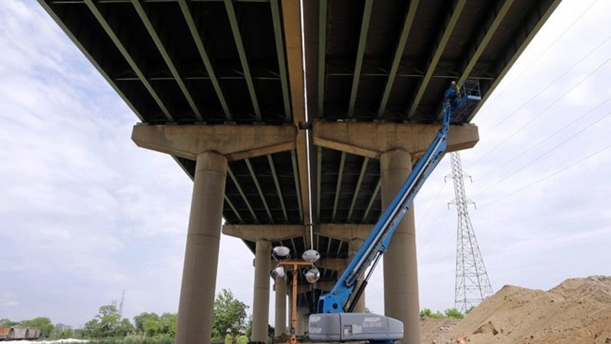 June 3, 2014: A worker inspects the underside of the Interstate 495 bridge over the Christina River near Wilmington, Del., after it was closed due to the discovery of tilting support columns.