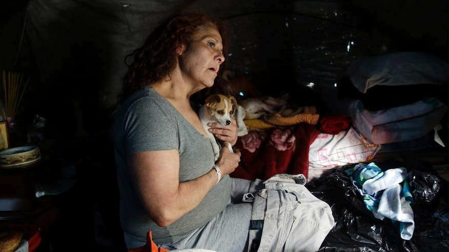 In this March 18, 2014 photo, Maria Esther Salazar holds a dog in her tent in the Jungle, a homeless encampment in San Jose, Calif. Salazar, a woman with a criminal record, two dogs, no phone and no identification had to find an apartment in one of the most expensive housing markets in the U.S., or the subsidy housing she qualified for could disappear. (AP Photo/Marcio Jose Sanchez)