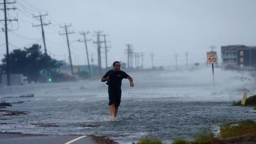 A man crosses a flooded Highway 64 as wind pushes water over the road as Hurricane Arthur passes through Nags Head, N.C., Friday, July 4, 2014. (AP Photo/Gerry Broome)