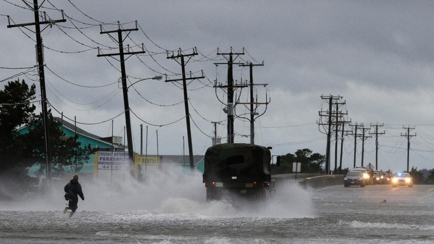 A military vehicle and a man navigate a flooded Highway 64 as wind pushes water over the road while Hurricane Arthur passes through Nags Head, N.C., Friday, July 4, 2014. (AP Photo/Gerry Broome)