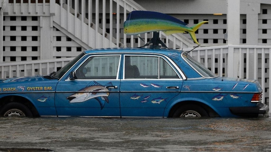 A vehicle sits in rising waters as Hurricane Arthur passes through the area in Nags Head, N.C., Friday, July 4, 2014. (AP Photo/Gerry Broome)