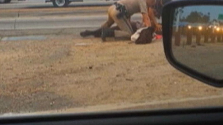 In this July 1, 2014 image made from video provided by motorist David Diaz, a California Highway Patrol officer, left, aided by another man, stand over a woman while punching her in the head on the shoulder of a Los Angeles freeway. The woman had been walking on Interstate 10 west of downtown Los Angeles, endangering herself and people in traffic, and the officer was trying to restrain her, CHP Assistant Chief Chris O'Quinn said at a news conference. The officer, who has not been identified, has been placed on administrative leave during an investigation. (AP Photo/David Diaz)