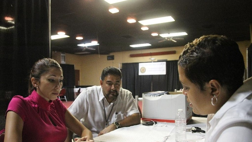 June 27, 2014: In this photo, veteran Rebecca King, left, talks with Veterans Affairs employee Joe Esparza, center, and American Legion official Verna Jones at the American Legion in El Paso, Texas.The American Legion is hosting crisis centers in different cities to help veterans get doctor's appointments and benefits from the Department of Veterans Affairs.