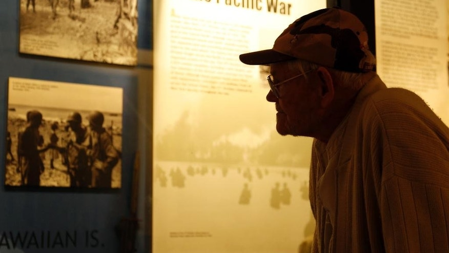 World War II veteran Arthur Robinson of Saratoga Springs, N.Y., looks at a display at the New York State Military Museum on Thursday, May 8, 2014, in Saratoga Springs. The Army's 27th Infantry Division, which Robinson served in, bore the brunt of Japan's largest mass suicide attack, launched before dawn on July 7, 1944, on the island of Saipan. The division's 105th Regiment saw more than 400 killed and 500 wounded during the attack by more than 3,000 Japanese soldiers and sailors. The 27th was a former New York National Guard unit that still had many New Yorkers among its ranks when it landed on Saipan after the U.S. Marines made the initial beach assault on June 15, 1944.   (AP Photo/Mike Groll)