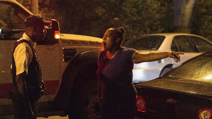 In this Sunday, July 6, 2014 photo, a woman talks to a Chicago police officer near the scene where a man was shot in the leg on the city's South Side. The Fourth of July weekend was a bloody one in Chicago, where at least nine people were shot to death and at least 60 others were wounded. (AP Photo/Sun-Times Media, Alex Wroblewski)  MANDATORY CREDIT, MAGS OUT, NO SALES