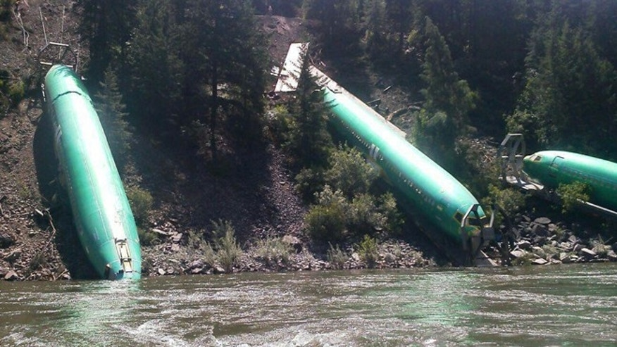 July 6, 2014: This photo by Jerry Compton provided by Wiley E. Waters Whitewater Rafting shows a freight train that derailed near Alberton in western Montana, sending three cars carrying aircraft components down a steep embankment and into the Clark Fork River on Thursday, July 3.  (AP/Wiley E. Waters Whitewater Rafting, Jerry Compton)