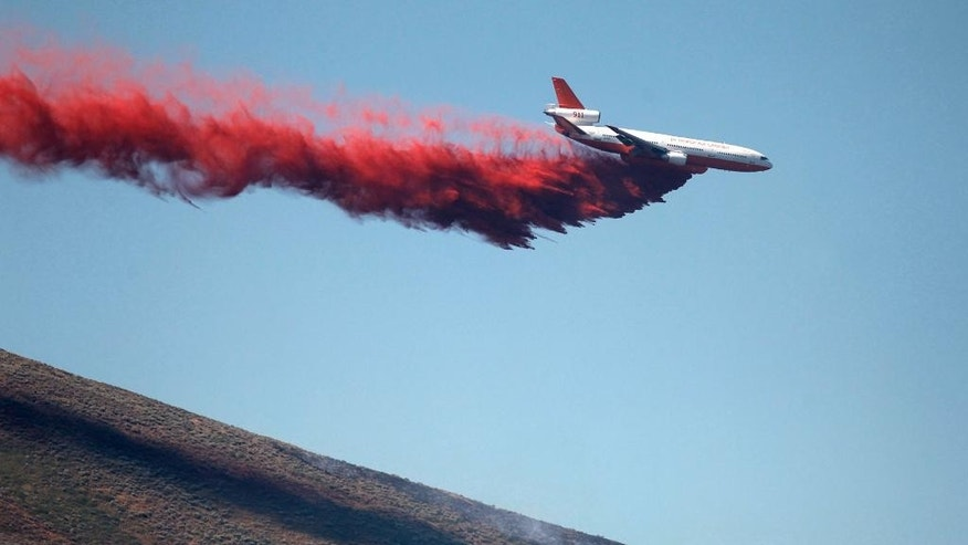 A DC-10 Air Tanker makes a drop on the Colorado Gulch fire on Monday, July 7, 2014 near Hailey, Idaho.  Idaho. In Idaho, all evacuations were lifted Monday as more crews were dispatched to the Colorado Gulch Fire in Blaine County as flames spread. The fire has blackened a square mile since it started Sunday, and officials hope to have it contained by Tuesday. (AP Photo/Times-News, Ashey Smith)