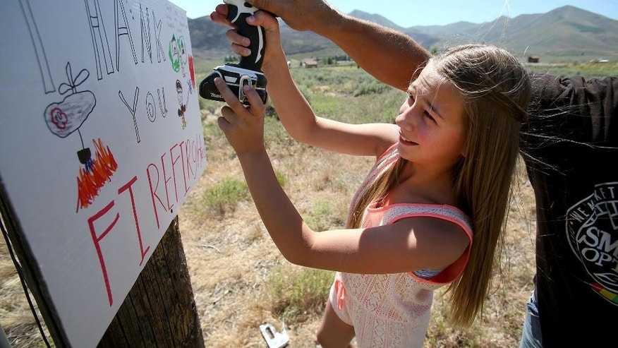 Britta Heaphy, 11, gets a hand from her father, Pete, as they hang a sign thanking firefighters who were battling the Colorado Gulch fire in their neighborhood on Monday, July 7, 2014 near Hailey, Idaho. In Idaho, all evacuations were lifted Monday as more crews were dispatched to the Colorado Gulch Fire in Blaine County as flames spread. The fire has blackened a square mile since it started Sunday, and officials hope to have it contained by Tuesday. (AP Photo/Times-News, Ashey Smith)