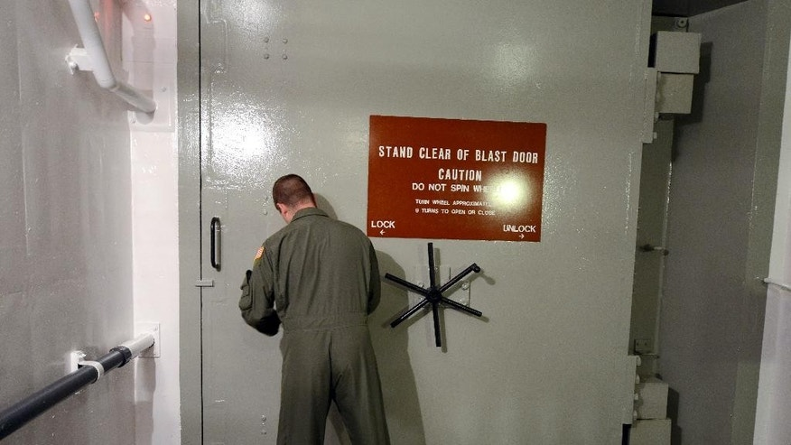 This photo taken June 24, 2014 shows 1st Lt. Phil Parentrau opening the blast door leading to the underground control room at  an ICBM launch control facility near Minot, N.D., on the Minot Air Force Base. The nuclear missiles hidden in plain view across the prairies of northwest North Dakota reveal one reason why trouble keeps finding the nuclear Air Force. (AP Photo/Charlie Riedel)