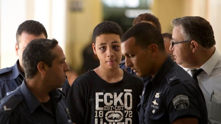 July 6, 2014: Tariq Abu Khdeir, 15, is escorted by Israeli prison guards during a court appearance, Jerusalem, Israel. (AP)