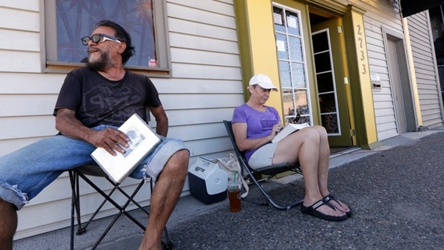 July 7, 2014: George Vargas, left, takes a seat next to first-in-line customer Deb Greene in front of the recreational marijuana store Cannabis City in Seattle. The store will be the first and only store initially in Seattle to legally sell recreational pot when sales begin Tuesday.