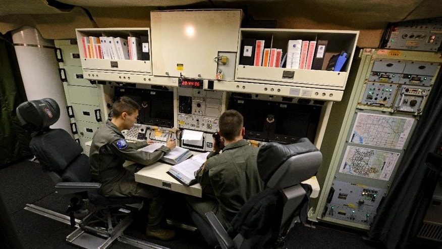 In this photo taken June 24, 2014, 2nd Lt. Oliver Parsons, right, and 1st Lt. Andy Parthum check systems in the underground control room where they work a 24-hour shift at an ICBM launch control facility near Minot, N.D., Minot Air Force Base. The crew is responsible for controlling and launching the 10 nuclear-tipped Minuteman 3 missiles located in remote launch sites under their command. (AP Photo/Charlie Riedel)