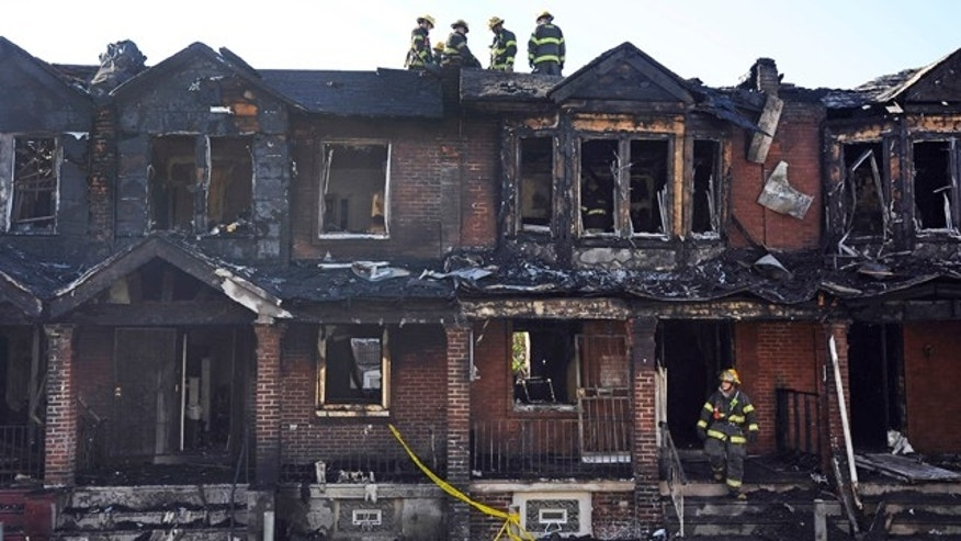 July 5, 2014: Philadelphia firefighters work on burned row homes. (AP Photo/Michael Perez)