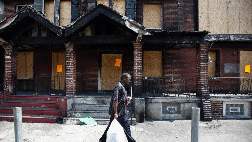 Solomon Johnson walks to his fire-damaged rowhouse, Tuesday, July 8, 2014, in Philadelphia. Johnson lived next door to a home where four young children died in a fast-moving blaze that engulfed at least 10 residences over the weekend. (AP Photo/Matt Slocum)