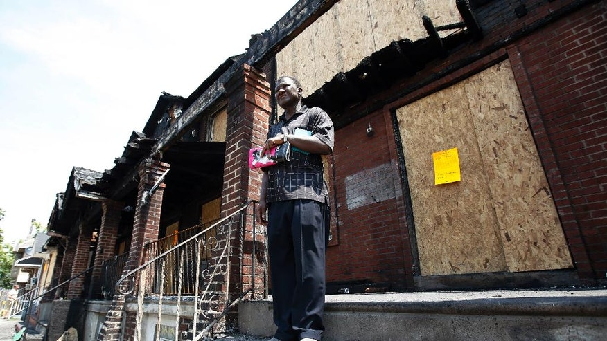 Solomon Johnson talks with a reporter on the steps of his fire-damaged rowhouse, Tuesday, July 8, 2014, in Philadelphia. Johnson lived next door to a rowhouse where four young children died in a fast-moving blaze that engulfed at least 10 residences over the weekend. (AP Photo/Matt Slocum)