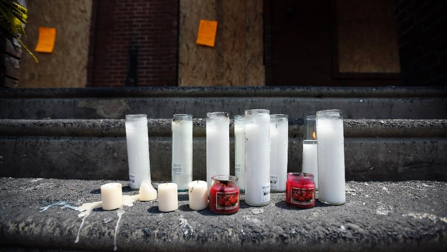 Candles burn on the steps of fire-damaged home, Tuesday, July 8, 2014, in Philadelphia, where four young children died over the weekend in a fast-moving blaze that engulfed at least 10 residences. (AP Photo/Matt Slocum)
