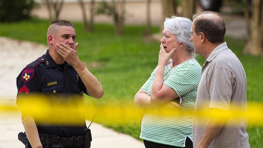 People stand with a law enforcement officer near the scene of a shooting Wednesday, July 9, 2014, in Spring, Texas. A Harris County Sheriff's Office statement says precinct deputy constables were called to the house about 6 p.m. Wednesday and found two adults and three children dead. Another child later died at a hospital. (AP Photo/Houston Chronicle, Brett Coomer)