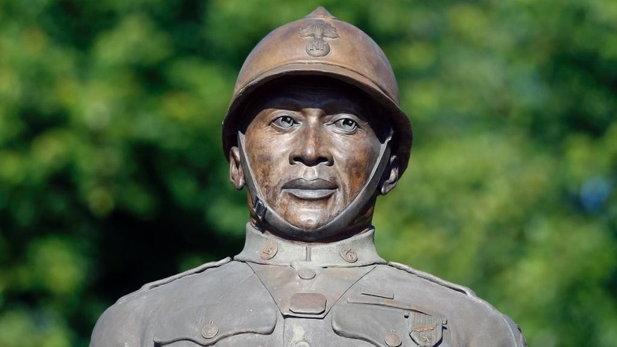 A statue of Henry Johnson is displayed in the Arbor Hill neighborhood on Thursday, July 10, 2014, in Albany, N.Y. U.S. Defense Secretary Chuck Hagel will consider whether the black World War I hero from Albany should be posthumously awarded the Medal of Honor nearly 100 years after he single-handedly fought off a German attack, killing several of the enemy and saving a comrade despite suffering serious wounds. Johnson was a solider in an all-black outfit, the 369th Infantry Regiment, a New York National Guard unit based in Manhattan and known as the Harlem Hellfighters. (AP Photo/Mike Groll)