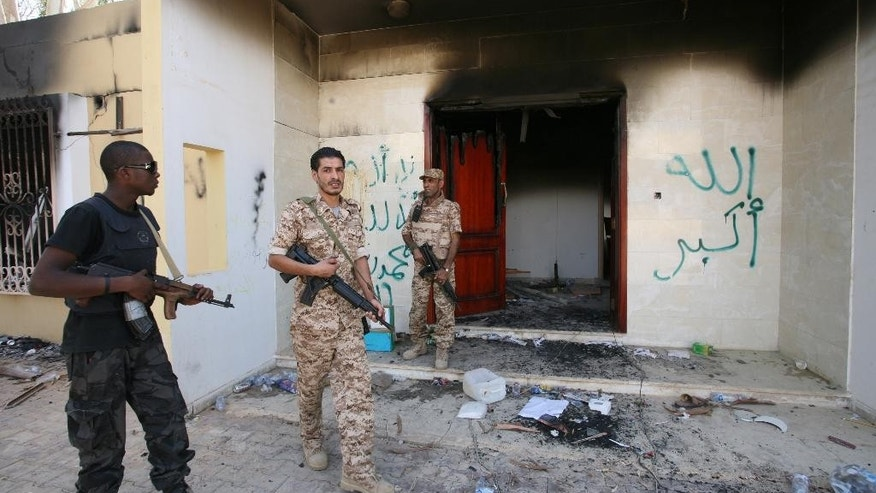 "FILE - This Sept. 14, 2012, file photo shows Libyan military guards as they check one of the U.S. Consulate's burnt out buildings after a deadly attack on Tuesday, September 11, 2012, in Benghazi. The testimony of nine military officers severely undermines claims by Republican lawmakers that a ""stand-down order"" held back military assets who could have saved the U.S. ambassador and three other Americans killed at a diplomatic outpost and CIA annex in Benghazi, Libya. (AP Photo/Mohammad Hannon, File)"