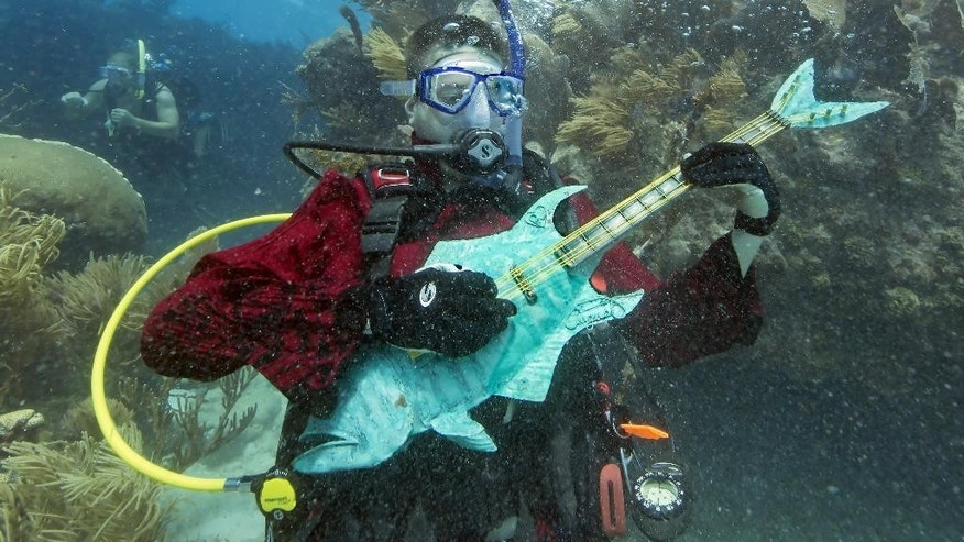 In this photo provided by the Florida Keys News Bureau, Mike Limerick pretends to play a mock musical instrument at the Lower Keys Underwater Music Festival on Saturday, July 12, 2014, in the Florida Keys National Marine Sanctuary. The subsea concert at Looe Key Reef, about six miles south of Big Pine Key, Fla., attracted almost 500 divers and snorkelers to listen to a local radio station's four-hour broadcast piped beneath the sea via underwater speakers. (AP Photo/Florida Keys News Bureau, Bob Care)