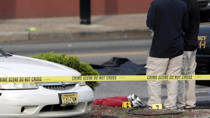A person lays on the ground near evidence markers as officials investigate the scene where a Jersey City Police Department officer was shot and killed while responding to a call at a 24-hour pharmacy, Sunday, July 13, 2014, in Jersey City, N.J.  Officer Melvin Santiago was shot in the head while still in his police vehicle as he and his partner responded to an armed robbery call  at about 4.a.m., Jersey City Mayor Steven Fulop said in a statement.  Fulop said officers responding to the robbery call shot and killed the man who shot Santiago. He was not immediately identified.(AP Photo/Julio Cortez)