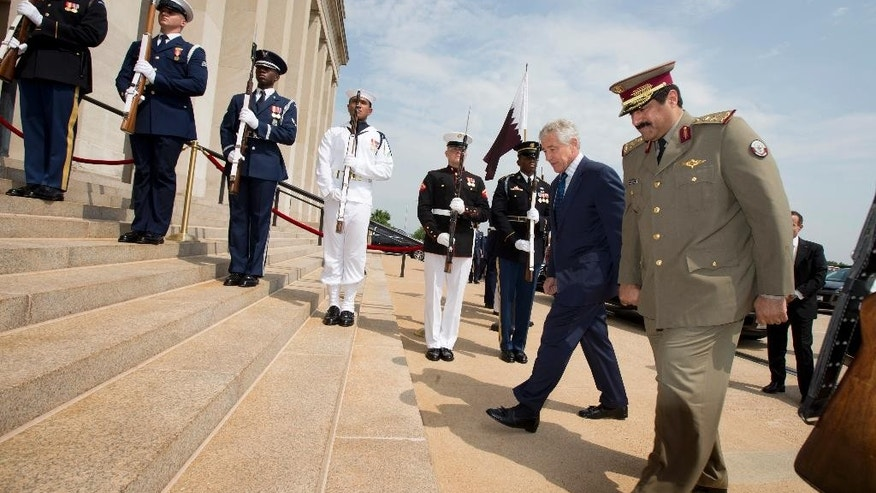 Defense Secretary Chuck Hagel welcomes Qatari Defense Minister Hamad bin Ali al-Attiyah, right, to the Pentagon, Monday, July 14, 2014, during an honor cordon. (AP Photo/Manuel Balce Ceneta)