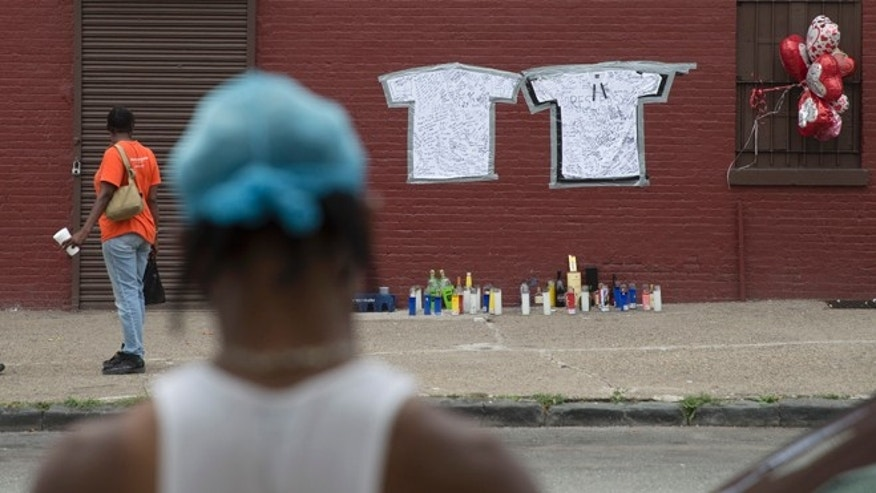 July 14: Pedestrians stand near a memorial to Lawrence Campbell, who allegedly shot and killed 23-year-old Jersey City police officer Melvin Santiago.
