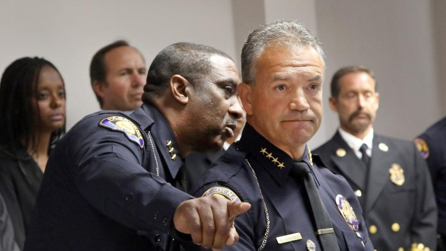 Pasadena Chief of Police Phillip Sanchez, right, is briefed by Deputy Chief of Police Darryl Qualls,  during a news conference in Pasedena, Calif., Monday July 14, 2014, on last Saturday's triple fatal shooting. Chief Sanchez praised two 911 operators for bringing a peaceful end to an armed standoff after three people were shot to death and two others wounded. (AP Photo/Nick Ut)