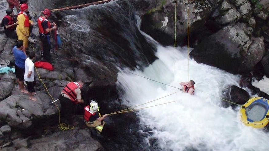In this July 14, 2014 photo released by the Skamania County Sheriff's Office, Skamania County sheriff's deputies and firefighters rescue John Napierkowski, bottom right, who was trapped in the water at Dougan Falls on the Washougal River in Washougal, Wash. Napierkowski was taken to a hospital after he was trapped in the cold water for about an hour. (AP Photo/Skamania County Sheriff's Office)