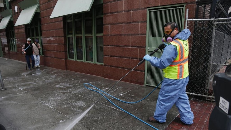 Eighi Hiastake, of the San Francisco Dept. of Public Works, washes a city sidewalk with a mixture of water and disinfectant on Tuesday, July 15, 2014, in San Francisco. In one of the most drastic responses yet to California's drought, state regulators on Tuesday will consider fines of up to $500 a day for people who waste water on landscaping, fountains, washing vehicles and other outdoor uses. The rules would prohibit watering of landscaping to the point that runoff spills onto sidewalks or streets. Hosing down sidewalks, driveways and other hard surfaces would be prohibited, as would washing vehicles without a shut-off nozzle. (AP Photo/Marcio Jose Sanchez)