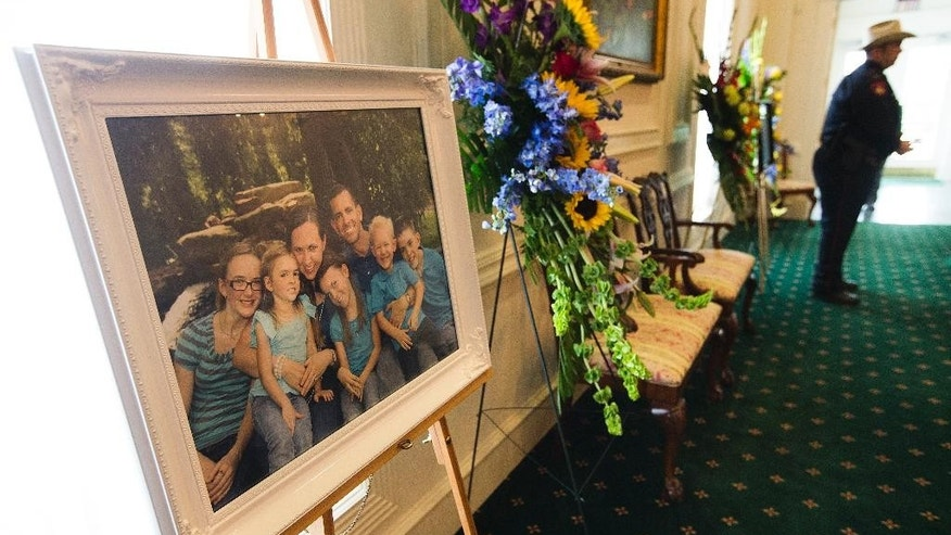 A family portrait of the Stephen and Katie Stay family is on display before visitation at Klein Funeral Home Tuesday, July 15, 2014, in Houston. Ron Lee Haskell has been charged in the shooting deaths of the six members of the Stay Family. (AP Photo/Houston Chronicle, Brett Coomer)
