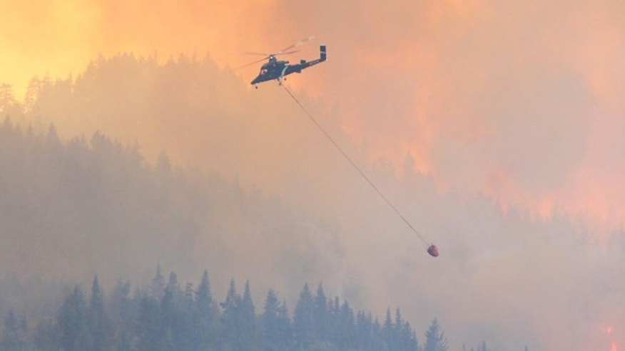 July 16, 2014: A helicopter flies over the Chiwaukum Creek Fire in central Washington state (Photo courtesy Q13Fox.com viewer submission)