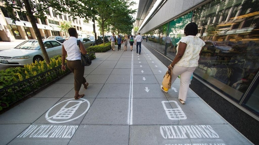 As part of their Mind Over Masses television show, National Geographic divided a one block-long sidewalk into two sections&#x3b; one for cell phone users and the other for those not using a cell phone in downtown Washington, Thursday, July 17, 2014.  The walkway warnings were put there by the brains behind a National Geographic television show as part of a behavioral science experiment. (AP Photo/Cliff Owen)