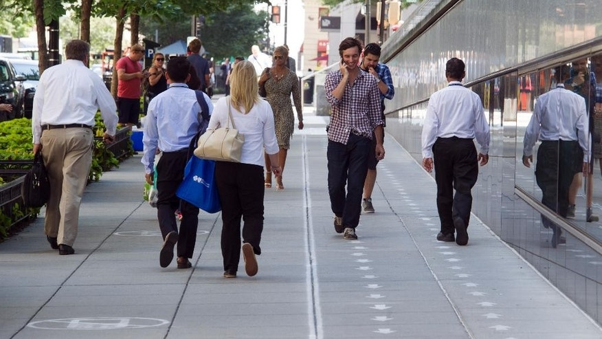 As part of their Mind Over Masses television show, National Geographic has divided a block-long sidewalk into two sections; one for cell phone users and the other for those not using a cell phone in downtown Washington, Thursday, July 17, 2014. The walkway warnings were put there by the brains behind a National Geographic television show as part of a behavioral science experiment.(AP Photo/Cliff Owen)