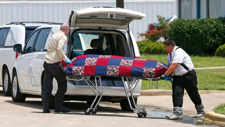 June 15, 2014: Authorities remove bodies from the Johnson Family Mortuary in east Fort Worth, Texas. (AP)